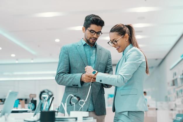 Mąż kupuje nowy inteligentny zegarek dla swojej uroczej żony. wnętrze sklepu technicznego.