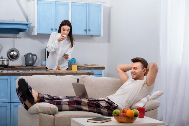 Mąż leży na kanapie, podczas gdy jego żona przygotowuje się do pracy.