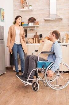 Mąż na wózku inwalidzkim z papierową torbą z supermarketu w kuchni rozmawia z żoną. niepełnosprawny, sparaliżowany, niepełnosprawny mężczyzna z niepełnosprawnością chodu, integrujący się po wypadku.