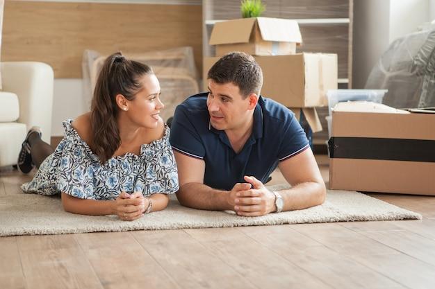 Mąż opowiadający historię swojej żonie siedząc na podłodze w ich nowym domu.
