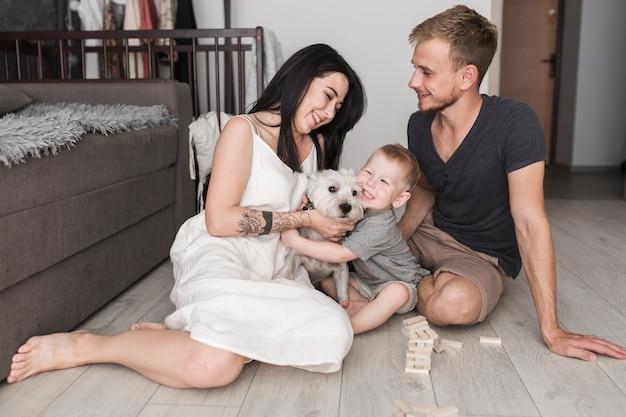 Mąż patrzeje jej żony bawić się z psim i uśmiechniętym synem w domu