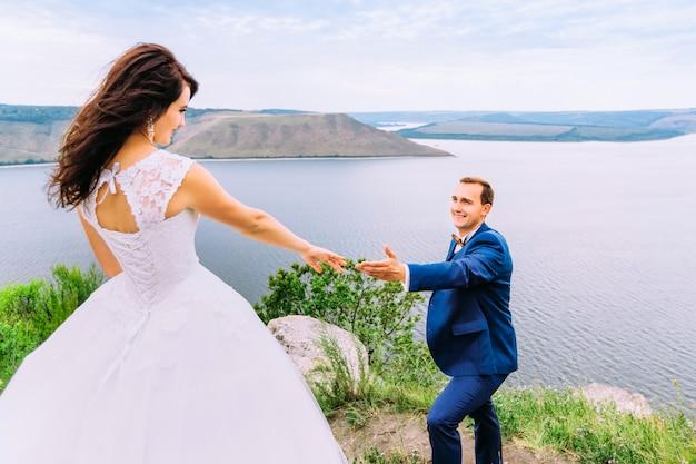 Mąż podając rękę do żony w sukni ślubnej
