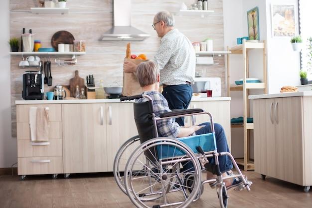 Mąż pomaga niepełnosprawny starszy kobieta na wózku inwalidzkim z papierową torbą spożywczy. . dojrzali ludzie ze świeżymi warzywami z targu. życie z osobą niepełnosprawną z niepełnosprawnością ruchową