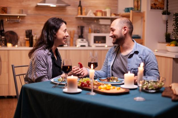 Mąż proponuje żonie poślubienie go w kuchni podczas romantycznej kolacji. mężczyzna składa oświadczyny swojej dziewczynie w kuchni podczas romantycznej kolacji. szczęśliwa kaukaska kobieta uśmiecha się zaniemówiona