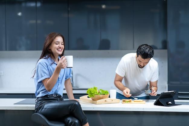 Mąż przygotowuje kanapkę warzywną dla żony, podczas gdy żona pije kawę. szczęśliwa rodzina spędza razem czas w domu.