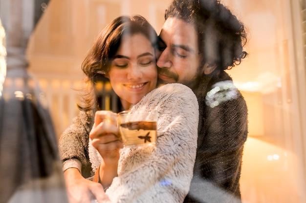Mąż przytula swoją żonę, podczas gdy ona trzyma filiżankę herbaty