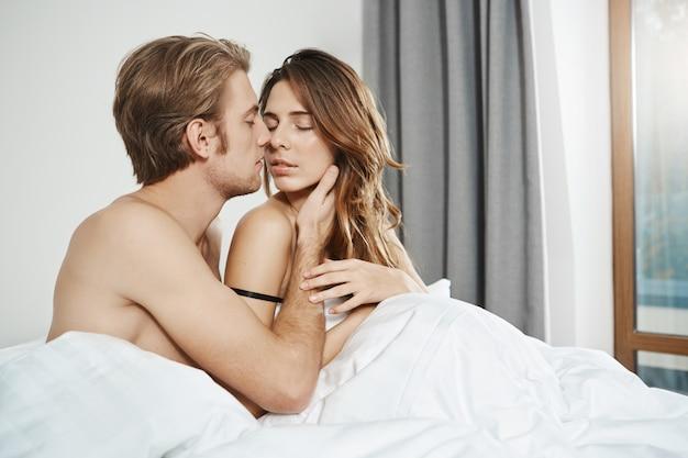 Mąż siedzi w łóżku z żoną, trzymając dłoń na jej twarzy i całując, podczas gdy jej oczy są zamknięte, a dłoń delikatnie dotyka jego ramienia. początek zmysłowej porannej gry wstępnej nowożeńców.