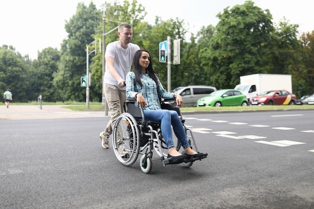 Mąż toczy wózek inwalidzki z młodą żoną