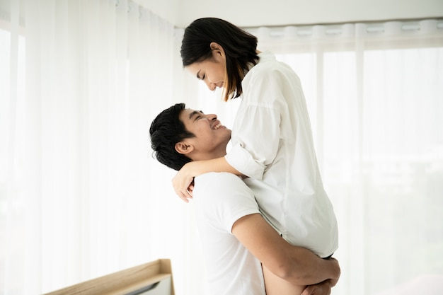Mąż trzyma żonę i całuje w sypialni, parze i związku. para w walentynki.