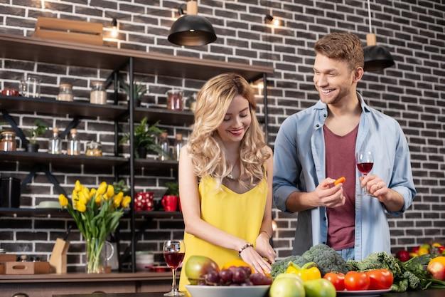 Mąż uśmiecha się. szczęśliwy, rozpromieniony brodaty mąż uśmiecha się szeroko i patrzy, jak jego żona gotuje obiad
