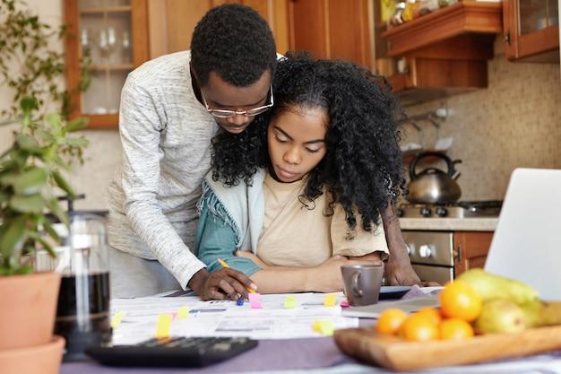 Mąż w okularach pomaga swojej pięknej żonie z papierkami, stoi obok niej i wyjaśnia coś na papierach. młoda afrykańska rodzina razem zarządzających finansami, siedząc przy kuchennym stole