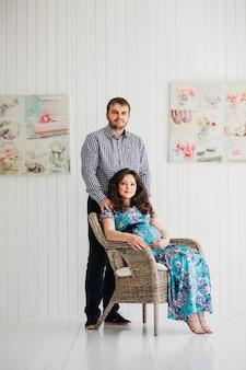 Mąż z żoną w ciąży siedzi na krześle z rattanu i uśmiecha się