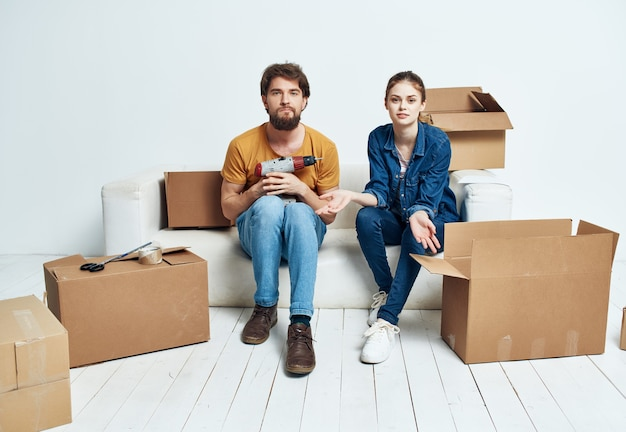 Mąż żona na kanapie w nowym mieszkaniu pudła z rzeczami w ruchu. zdjęcie wysokiej jakości