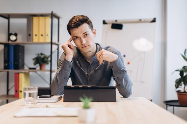Mdłości i zmęczenie sfrustrowany młody człowiek masuje nos i ma zamknięte oczy, siedząc w swoim miejscu pracy w biurze