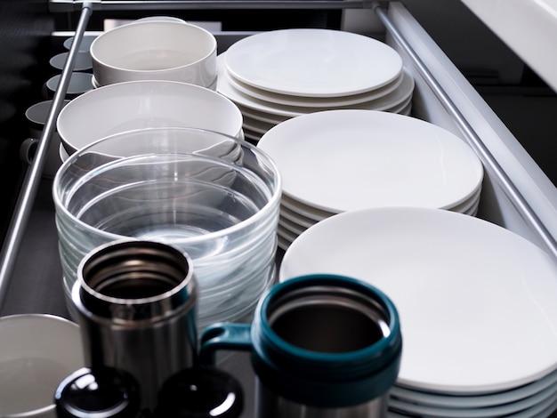 Meble kuchenne z szafką do przechowywania pojemników naczynia kuchenne z naczyniami ceramicznymi i szklanym kubkiem.