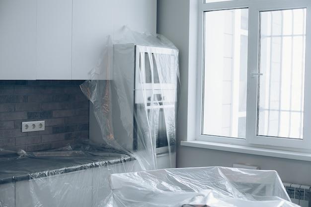 Meble pokryte plastikiem w kuchni. naprawy w mieszkaniu. niedokończone mieszkanie