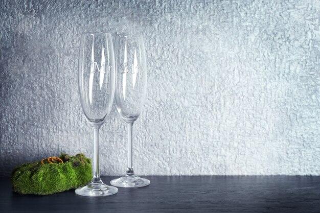 Mech z obrączkami i kieliszkami do szampana na stole i szarym tle ściany