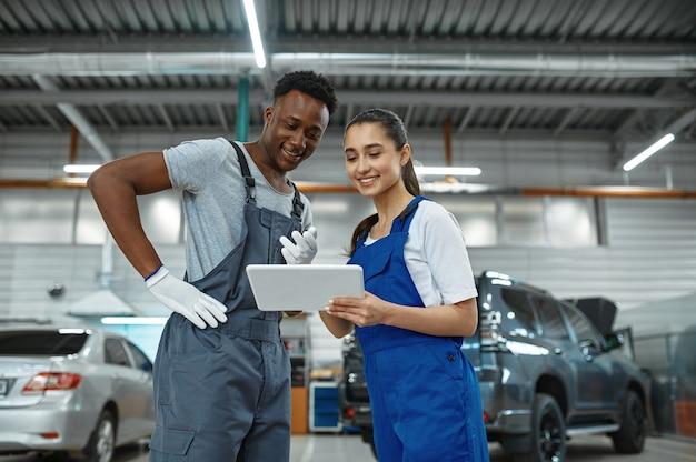 Mechanicy i kobiety sprawdzają silnik, serwis samochodowy. warsztat samochodowy, mężczyźni w mundurach, wnętrze stacji samochodowej. profesjonalna autodiagnostyka
