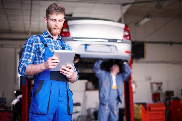 Mechanicy naprawiający samochód w warsztacie