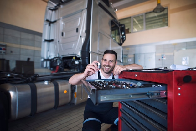 Mechanicy pojazdów stoją przy wózku narzędziowym i wybierają odpowiednie narzędzie do obsługi samochodów ciężarowych