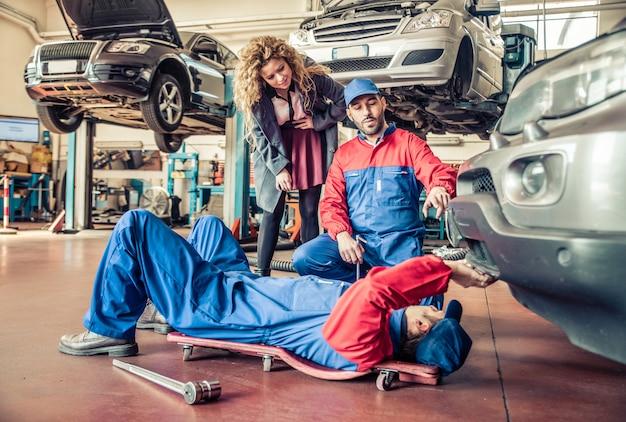 Mechanicy pracujący na uszkodzonym samochodzie