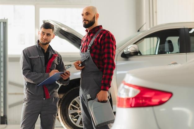 Mechanicy pracujący przy samochodzie płci męskiej i żeńskiej