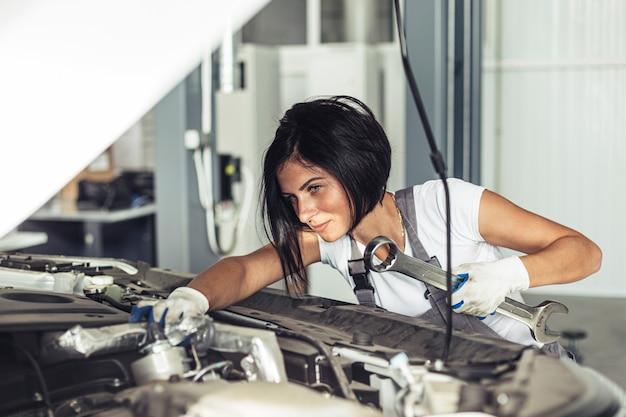 Mechaniczna kobieta naprawia samochód