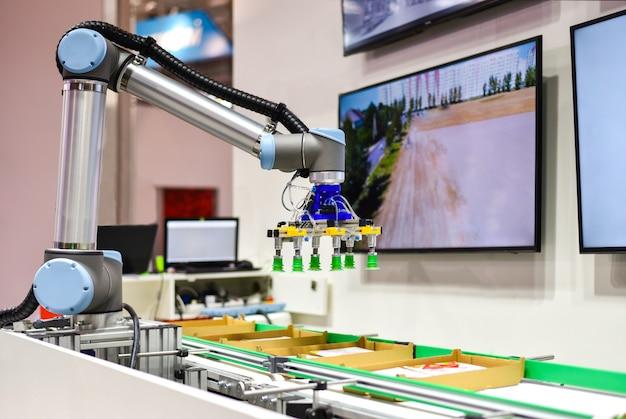 Mechaniczny robot ze sztuczną inteligencją sortuje produkty na przenośniku