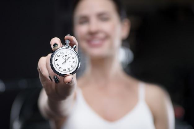 Mechaniczny stoper w kobiecej dłoni. lekkoatletka z tarczą zegara. koncepcja fitness i sportu