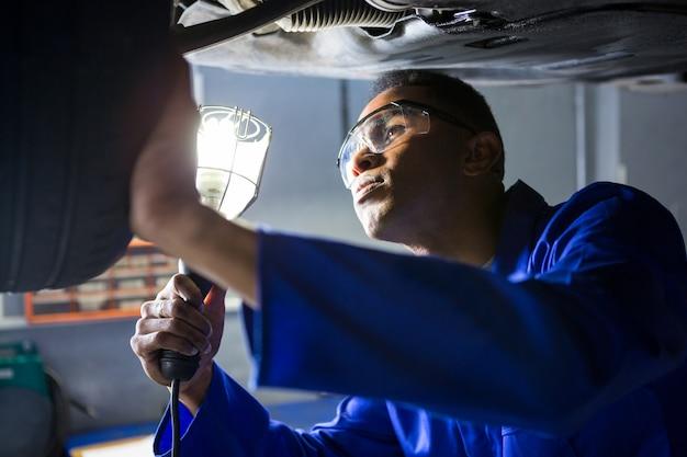 Mechanik badając opona samochodu za pomocą latarki