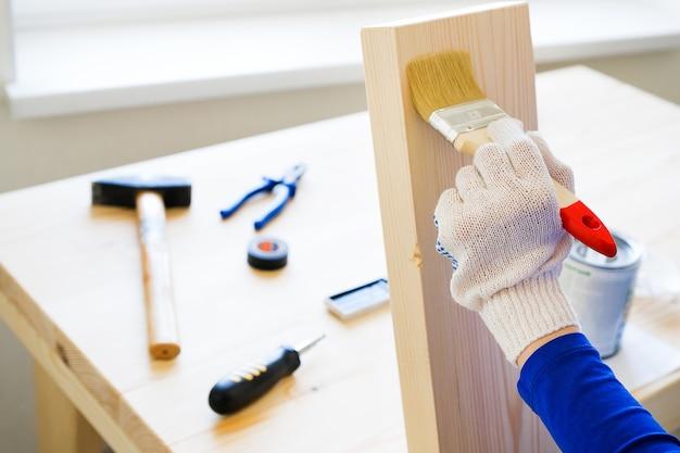 Mechanik, cieśla, zatrudniony pracownik stosuje lakier ochronny lub pędzel na drewnianej desce. rękawiczki, narzędzia budowlane w pobliżu. koncepcja remontu domu i profesjonalnego budownictwa.