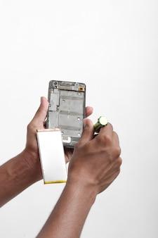 Mechanik demontażu smartfona za pomocą śrubokręta.