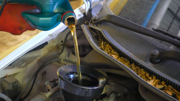 Mechanik drenujący olej silnikowy z samochodu do wymiany oleju w sklepie auto