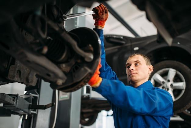 Mechanik kluczem naprawia zawieszenie samochodu.