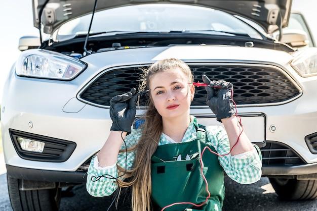 Mechanik kobieta szukający problemów z silnikiem samochodowym