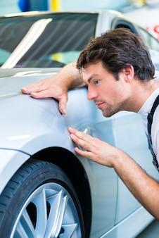 Mechanik kontrolujący lakier w warsztacie samochodowym
