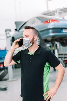 Mechanik kupujący części do samochodu noszący maskę chirurgiczną