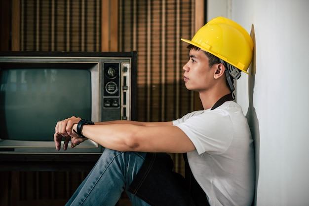 Mechanik ma na sobie żółty kapelusz i ręce spoczywające na kolanach.