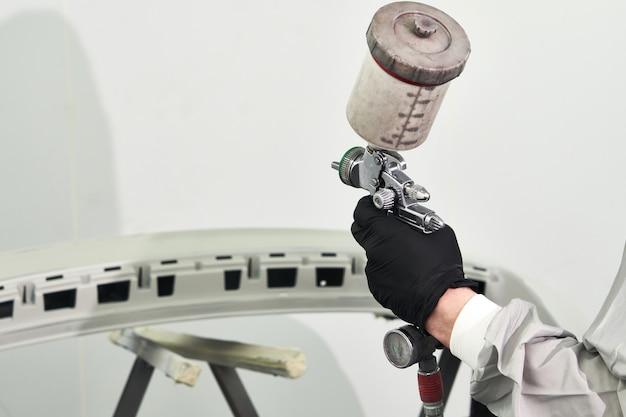 Mechanik malujący zderzak samochodu z opryskiwaczem w kabinie lakierniczej w serwisie samochodowym