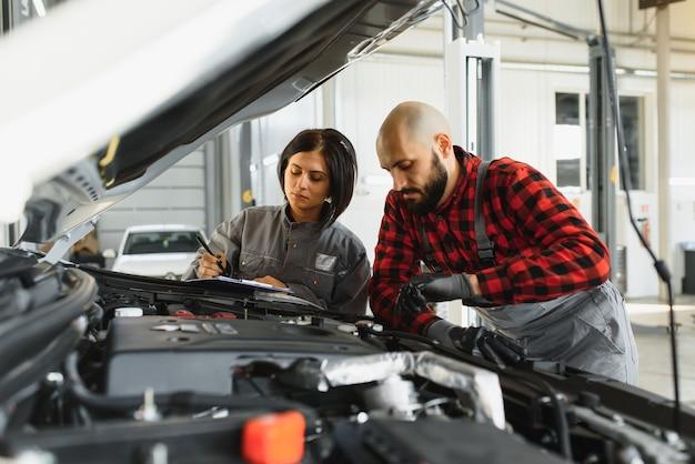 Mechanik mężczyzn z kluczem naprawy silnika samochodu w warsztacie