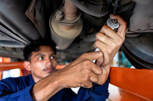 Mechanik mężczyzna patrzy na lampkę silnika. samochód serwisowy w garażu to samochód z listą kontrolną papieru. samochód serwisowy, naprawa, koncepcja konserwacji. technik robi listę kontrolną do naprawy maszyny samochód w garażu.
