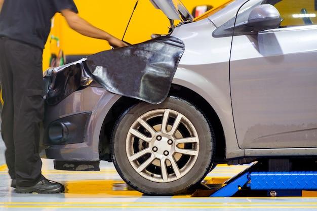 Mechanik mężczyzna sprawdzanie problemu z przodu samochodu silnika w garażu
