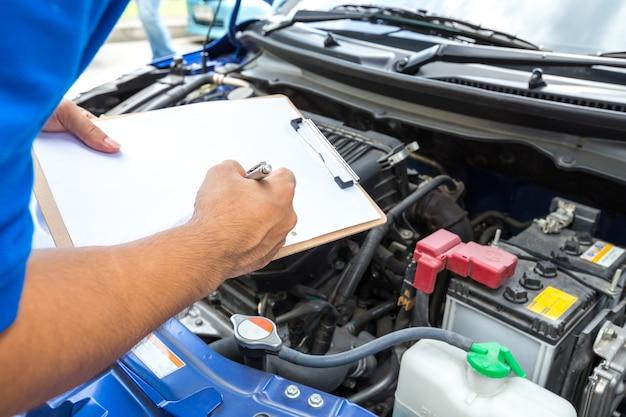 Mechanik mężczyzna trzyma schowek i sprawdza samochód