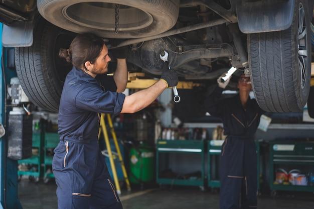 Mechanik mężczyzna za pomocą narzędzia klucza do naprawy i konserwacji samochodu w warsztacie samochodowym