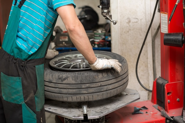 Mechanik mężczyzna zmienia montaż opon samochodowych.