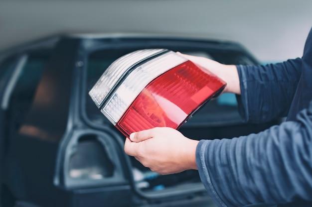 Mechanik montuje tylne światła w nowym samochodzie w serwisie samochodowym. mężczyzna trzyma w rękach reflektor.