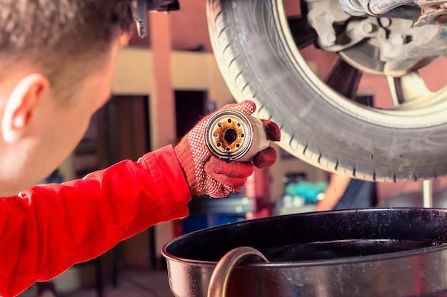 Mechanik motorowy w mundurze pracuje pod podniesionym samochodem i wymienia olej silnikowy