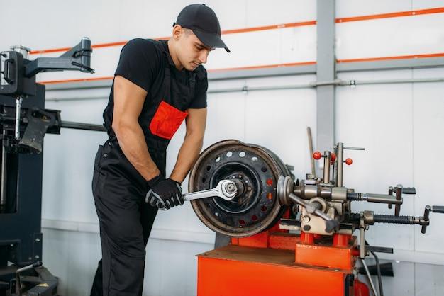 Mechanik naprawia zgnieciony dysk, serwis opon. mężczyzna naprawiający oponę samochodową w garażu, profesjonalny przegląd samochodowy w warsztacie
