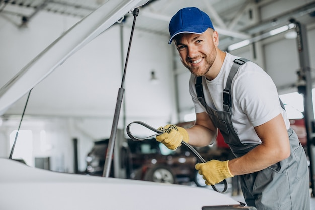 Mechanik naprawiający samochód w serwisie samochodowym