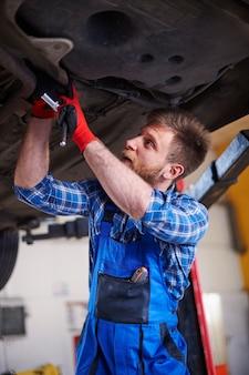 Mechanik naprawiający samochód w warsztacie